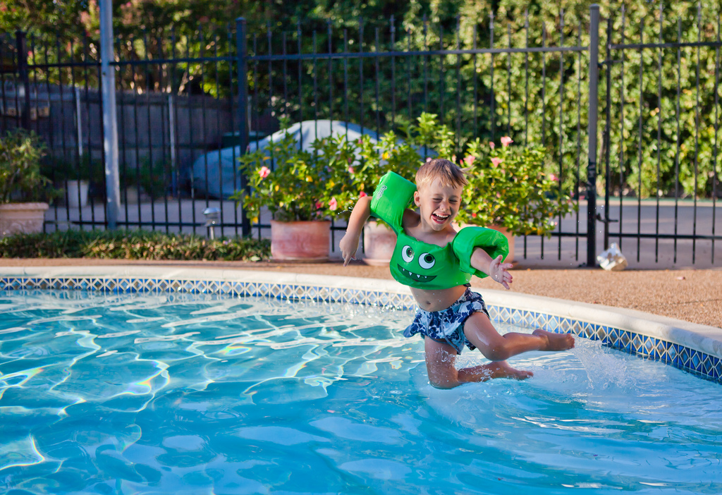 boy jumping into a swimming pool
